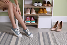 Woman Putting On Stylish Shoes Near Shelving Unit At Home, Closeup. Storage Idea