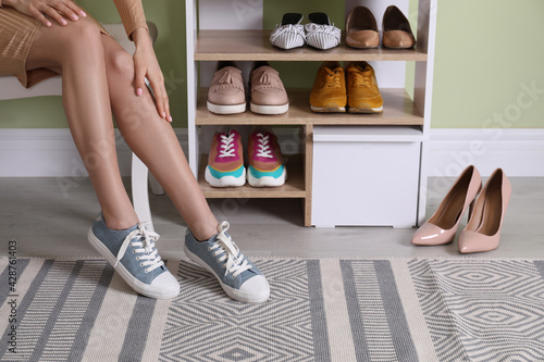 Canvas Woman putting on stylish shoes near shelving unit at home, closeup