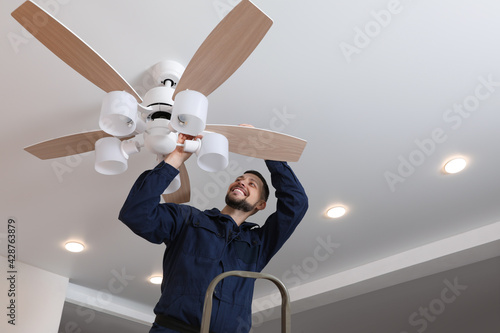 Fényképezés Electrician repairing ceiling fan with lamps indoors