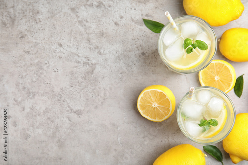 Obraz Cool freshly made lemonade and fruits on grey table, flat lay. Space for text - fototapety do salonu