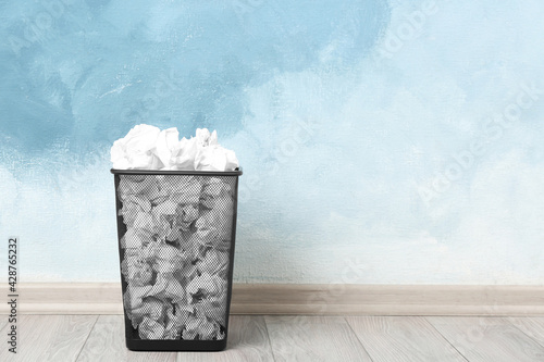 Basket with crumpled paper near light blue wall. Space for text
