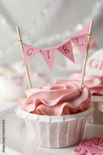 Obraz Delicious cupcake with pink cream and Girl topper for baby shower on plate, closeup - fototapety do salonu