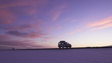 Panoramic Landscape Shot Of Volkswagen Campervan Driving On Highway In Iceland With Purple Sky While Sunset.