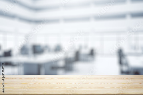Blank wooden tabletop with bright furnished office on background, mockup - fototapety na wymiar