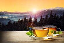 Cups Of Hot Tea On Wooden Table And Beautiful Winter Landscape On Background