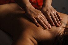 Hands Massaging Women's Back In The Spa Salon