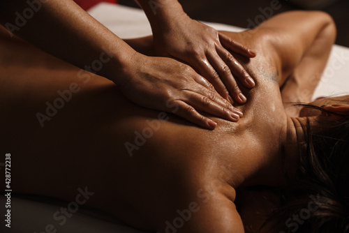 Foto Hands massaging women's back in the spa salon