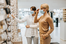Beautiful And Fashionable Woman Choosing Eyeglasses Frame In Modern Optical Store. Female Seller Specialist Helps Her To Make Right Decision. They Are Wearing Protective Face Mask.