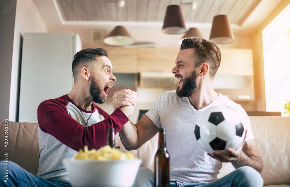 Two best friends and fans of football watching some sport match on the TV and drinking beers and eating snacks while cheering for the team on the couch