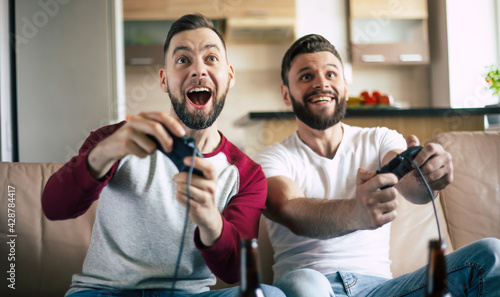 Fotografie, Obraz Excited smiling men playing in video games on tv at home on the couch