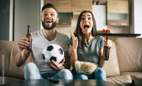 Fotografia, Obraz Happy fans couple is watching some football match in TV with snacks, beers and b