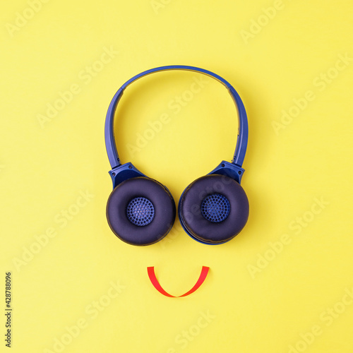 Fototapeta Headphones on a yellow background in the form of a happy face with a smile - Min