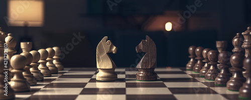 Fotografie, Obraz Chess pieces arranged on the chessboard and knights facing each other