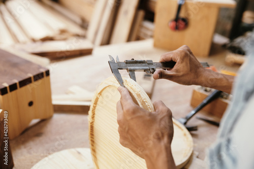 Hands of carpenter using vernier caliper to measure thickness of round wood board