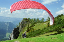 Skydiver In Pairs In The Alps Just Before Takeoff. It Is Now Time To Take Off! Alpine Panorama In The Background. Since One Gets Equal To Fly Itself. Normal Perspective.