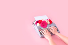 Woman Hands Typing On Vintage Typewriter. Flower Spring Concept With Copy Space.