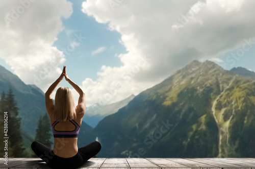 Fototapeta premium Young woman practicing yoga in the nature. female happiness. Landscape background