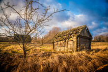 Abandoned Wooden House In A Field With Dry Grass And Gloomy Cloudy Sky