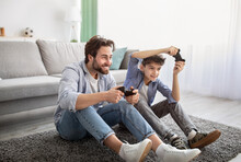 Videogames Concept. Joyful Father And Son Competing In Online Games, Holding Joysticks While Sitting On Carpet