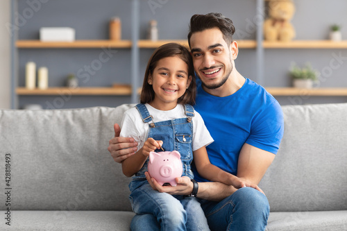Canvas Print Little girl and dad saving money in piggy bank