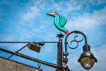 Painted Wooden Turquoise Bird Mounted On Grungy Metal Sign And Light Post Under Mottled Blue Clouded Sky In Funky Location - Close-up