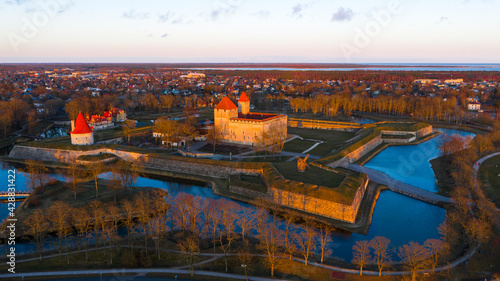 Leinwand Poster Aerial view to the sunset colored coastal historic medieval fortress with the su