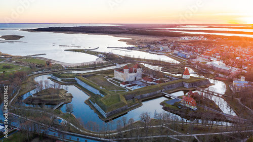 Obraz na plátne Aerial view to the sunset colored coastal historic medieval fortress with the su