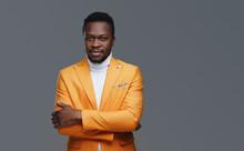 Black Fashion Guy In Orange Coat Against Gray Background