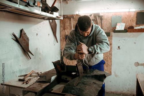 Fotografering tinsmith blacksmith use hammer working in his workshop