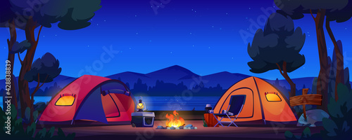 Foto Camping tents on river bank, mountains and night sky on background, bonfire and lantern lamp on portable fridge, chair and flashlight