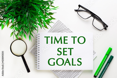 On a white background lies a notebook with words TIME TO SET GOALS, glasses, a magnifying glass, green markers and a green plant