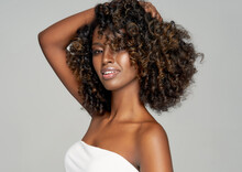 Portrait Of Happy Black Woman Isolated On Gray With Hand In Her Afro Hairstyle