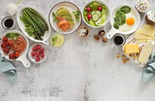 Breakfast Or Brunch Food Table. Meal Variety With Fried Egg, Asparagus, Avocado And Smoked Salmon Sandwich, Cheese Platter And Various Of Desserts. Overhead View