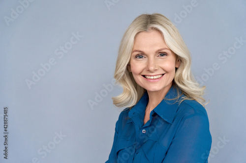 Happy smiling mature 50 years old female psychologist portrait looking at camera. Closeup headshot of sophisticated business woman isolated on grey background advertising products and services. - fototapety na wymiar