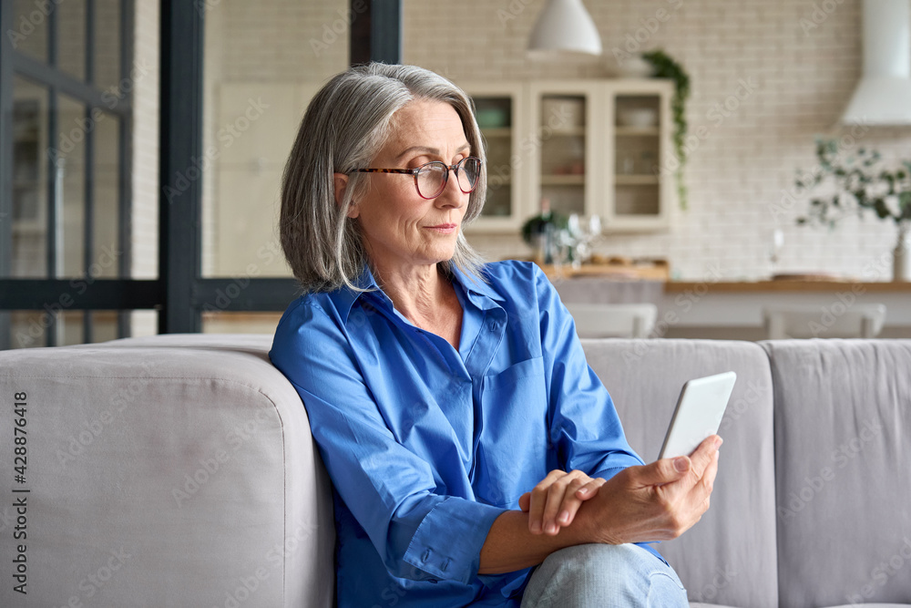 Fototapeta Serious mature middle age senior woman at home on couch holding mobile cellphone, reading news or watching online learning class having video call using mobile application.