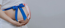 A Woman Holds Her Belly With Her Hands With A Blue And Pink Ribbon.