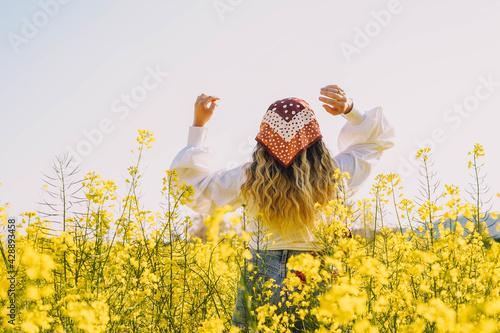 Bella mujer paseando en un día soleado de primavera por un campo de flores