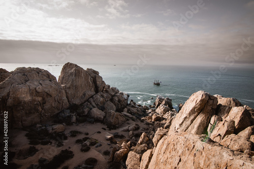 Obraz na plátně rocks on the beach and a pirate ship