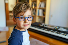 Small Caucasian Boy Sitting By Electric Piano Making Music At Home Leisure Activity Growing Up Education And Art Concept Playful Child Having Fun At Home Alone Looking To The Camera Copy Space