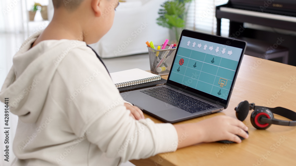 Fototapeta Young asia student kid remotely learn online at home in unplugged coding in STEM, STEAM, algorithms logical mathematics engineering science technology computer code in robotics for kids concept.