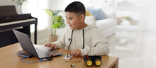 Young Asia Student Remotely Learn Online At Home In Coding Robot Car And Electronic Board Cable In STEM, STEAM, Mathematics Engineering Science Technology Computer Code In Robotics For Kids Concept.
