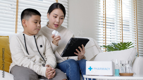 Young asia parents and son talk to doctor on cellphone videocall conference medical app in pediatric care online telehealth telemedicine online service hospital quarantine social distance at home.