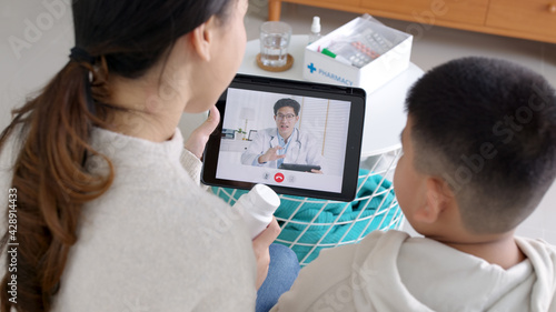 Over shoulder view of young asia parents and son talk to doctor on cellphone videocall conference medical app in telehealth telemedicine online service hospital quarantine social distance at home.