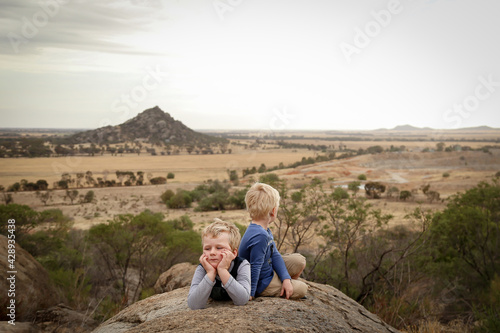 Fotografia, Obraz Little boys sitting on rock during bushwalk with view of Pyramid Hill, Victoria Australia in the background
