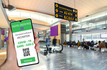 The Digital Green Pass Of The European Union With The QR Code On The Screen Of A Mobile Held By A Hand With Blurred Airport In The Background.