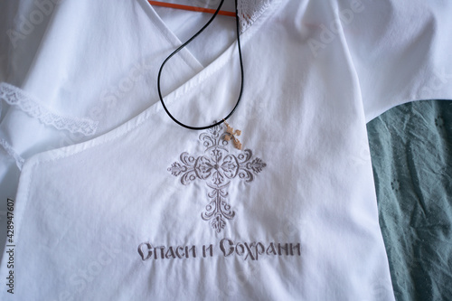 golden Orthodox cross on white christening shirt for the child with embroidery Fotobehang