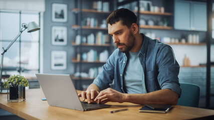 Handsome Caucasian Man Working on Laptop Computer while Sitting on a Sofa Couch in Stylish Cozy Living Room. Freelancer Working From Home. Browsing Internet, Using Social Networks, Being Serious.