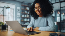 Beautiful Authentic Latina Female With Afro Hair Sitting At A Desk In A Cozy Living Room And Using Laptop Computer At Home. She's Browsing The Internet And Checking Videos On Social Networks.