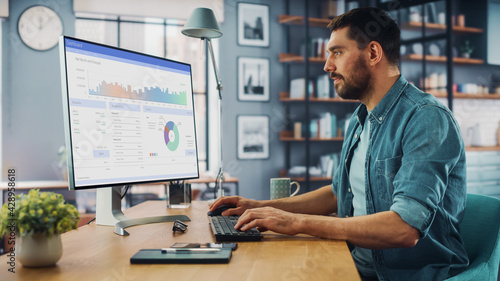 Caucasian Specialist Working on Desktop Computer in Creative Home Living Room. Freelance Male is Doing Market Analysis and Creates Report with Charts for Clients and Employer. - fototapety na wymiar