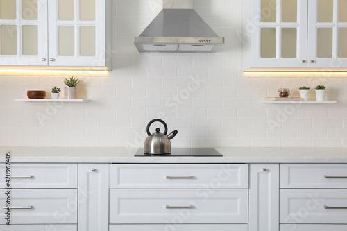 Elegant kitchen interior with modern stove and stylish furniture